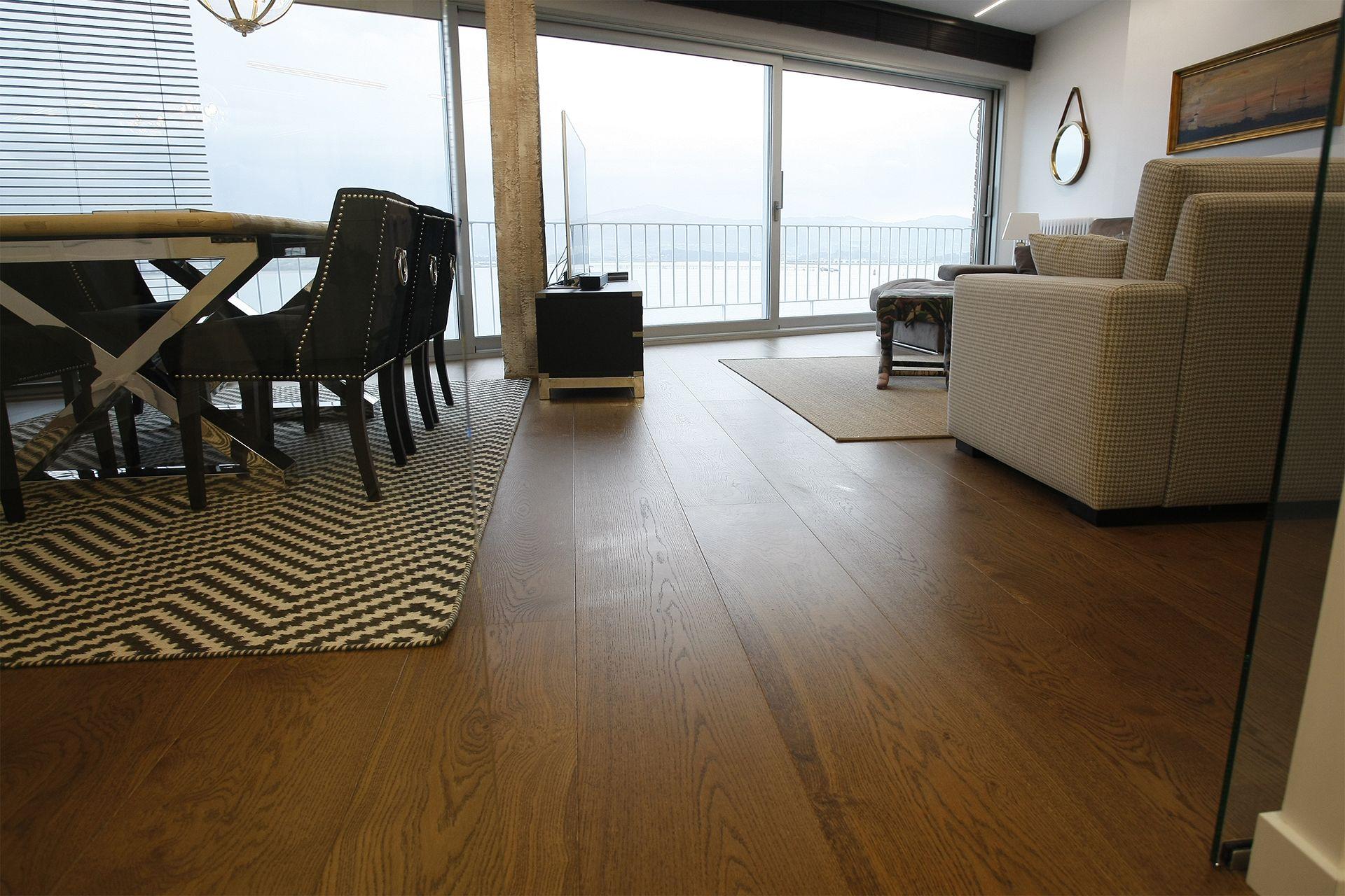 Salón con vista al mar con tarima laminada de abedul SURCO Heritage, color cognac, instalado por TPI